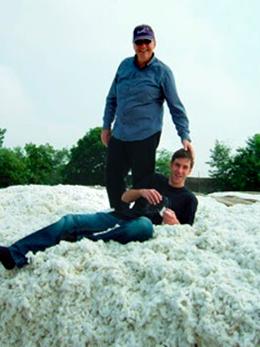 山積みにされたオーガニックコットンの上で。<br /> REMEI社長のHohmann親子